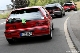 Red Honda Civic EF9 drives over a tip behind two CRX EE8