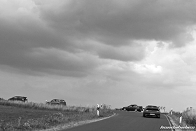 Black and white photo of a group of Hondas under dark clouds