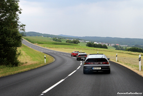 A red Honda Civic EF9 drives in front of two dark CRX EF8 through a curve