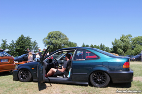 A man sits in a green low 2DR Honda Civic