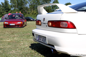 Rear of a white Integra DC2 in front of a red Civic Sedan EG8