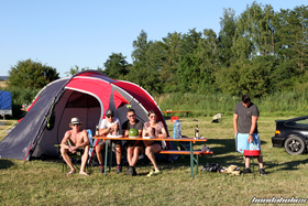People are sitting in the sun in front of a tent