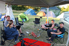 Honda-Fans sitting on camping chairs under a tent